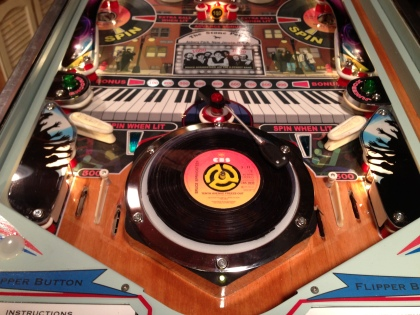 """A 45 Record sits on the turntable, waiting for a ball to hit a """"SPIN"""" hole."""